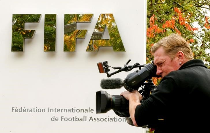A cameraman stands in front of FIFA's headquarters in Zurich