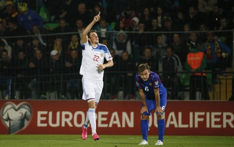 Russia's Dzyuba celebrates his goal as Moldova's Jardan reacts during their Euro 2016 group G qualifying soccer match against Moldova at Zimbru stadium in Chisinau