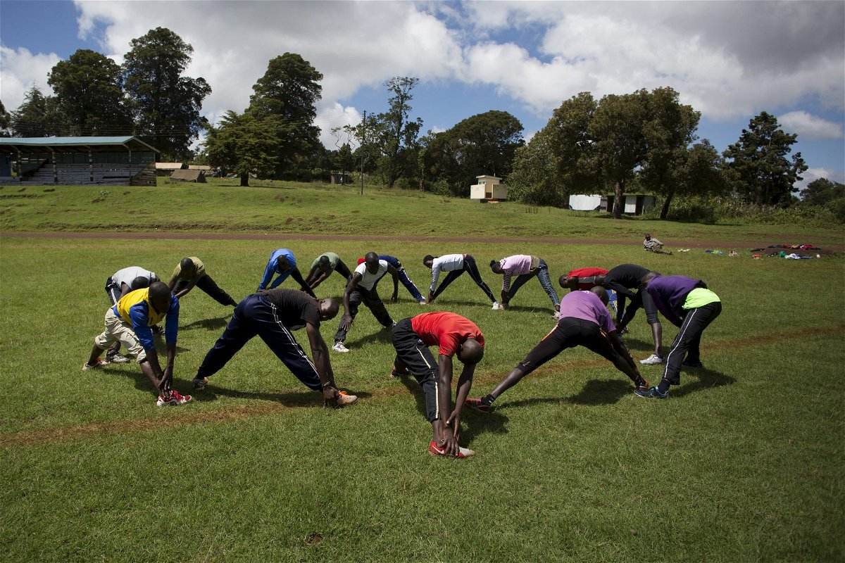 Athletes stretch during a training session on the training grounds in the town of Iten in western Kenya.