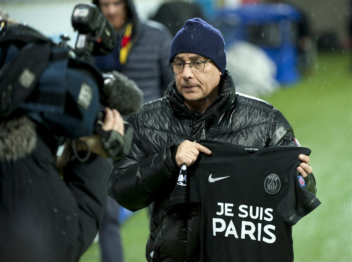 A reporter shows a Paris Saint Germain shirt with 'Je suis Paris' written on it for a TV-camera during a training session at the Malmo New Stadium in Malmo, Sweden, November 24, 2015. REUTERS/Bjorn Lindgren/TT News Agency