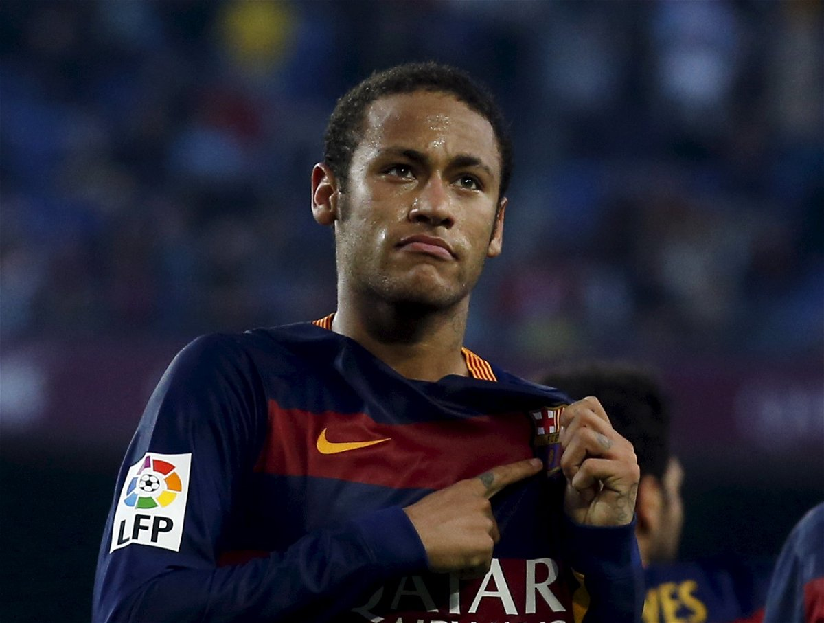 Neymar in FC Barcelona jersey pointing towards the emblem