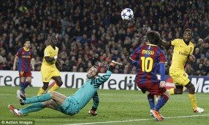 Messi flicks the ball over Almunia as he readies himself to put the ball in the net