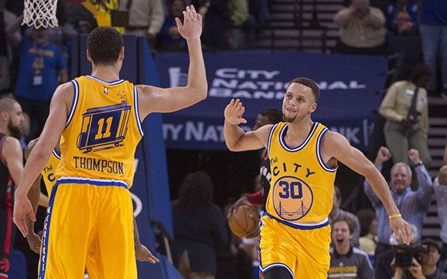 Stephen Curry giving a hi-five to Klay Thompson
