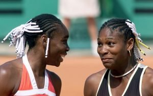 Venus Williams, left, and her sister Serena Williams share a light moment during their doubles tennis match against Els Callens of Belgium and Rita Grande of Italy at the French Open at Roland Garros stadium in Paris Wednesday, June 2, 1999. (AP Photo/Laurent Rebours) ORG XMIT: ROG131