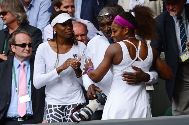 US player Serena Williams (R) climbs up into the Royal Box to embrace her father Richard and sister Venus Williams (L) after her women's singles final victory over Poland's Agnieszka Radwanska on day 12 of the 2012 Wimbledon Championships tennis tournament at the All England Tennis Club in Wimbledon, southwest London, on July 7, 2012. Serena Williams won the match 6-1, 5-7, 6-2. AFP PHOTO/ LEON NEAL RESTRICTED TO EDITORIAL USE (Photo by LEON NEAL / AFP) (Photo credit should read LEON NEAL/AFP via Getty Images)