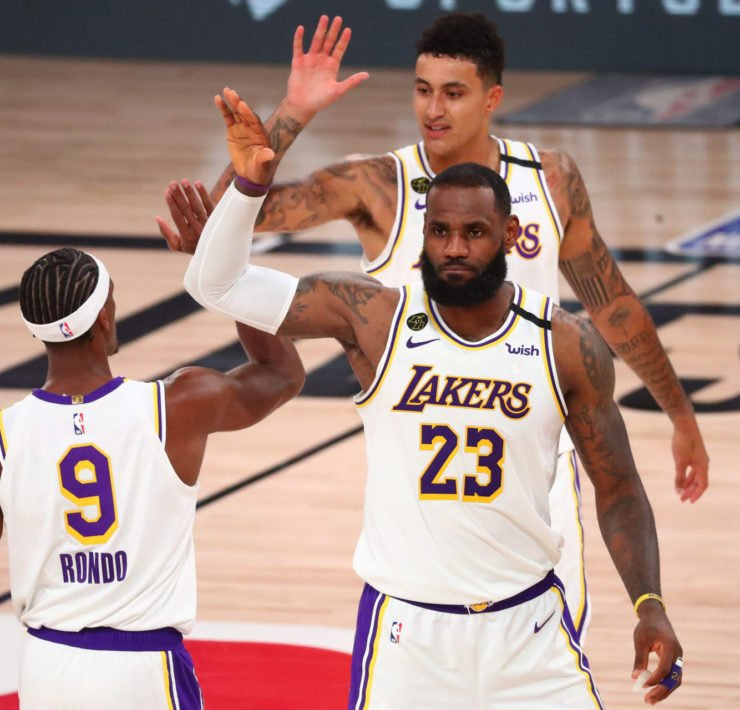 Los Angeles Lakers forward LeBron James celebrates with guard Rajon Rondo and forward Kyle Kuzma (top) during game three in the second round of the 2020 NBA Playoffs.