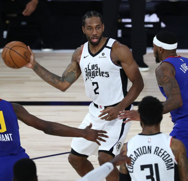 LA Clippers forward Kawhi Leonard passes the ball against Denver Nuggets forwards in game 6.