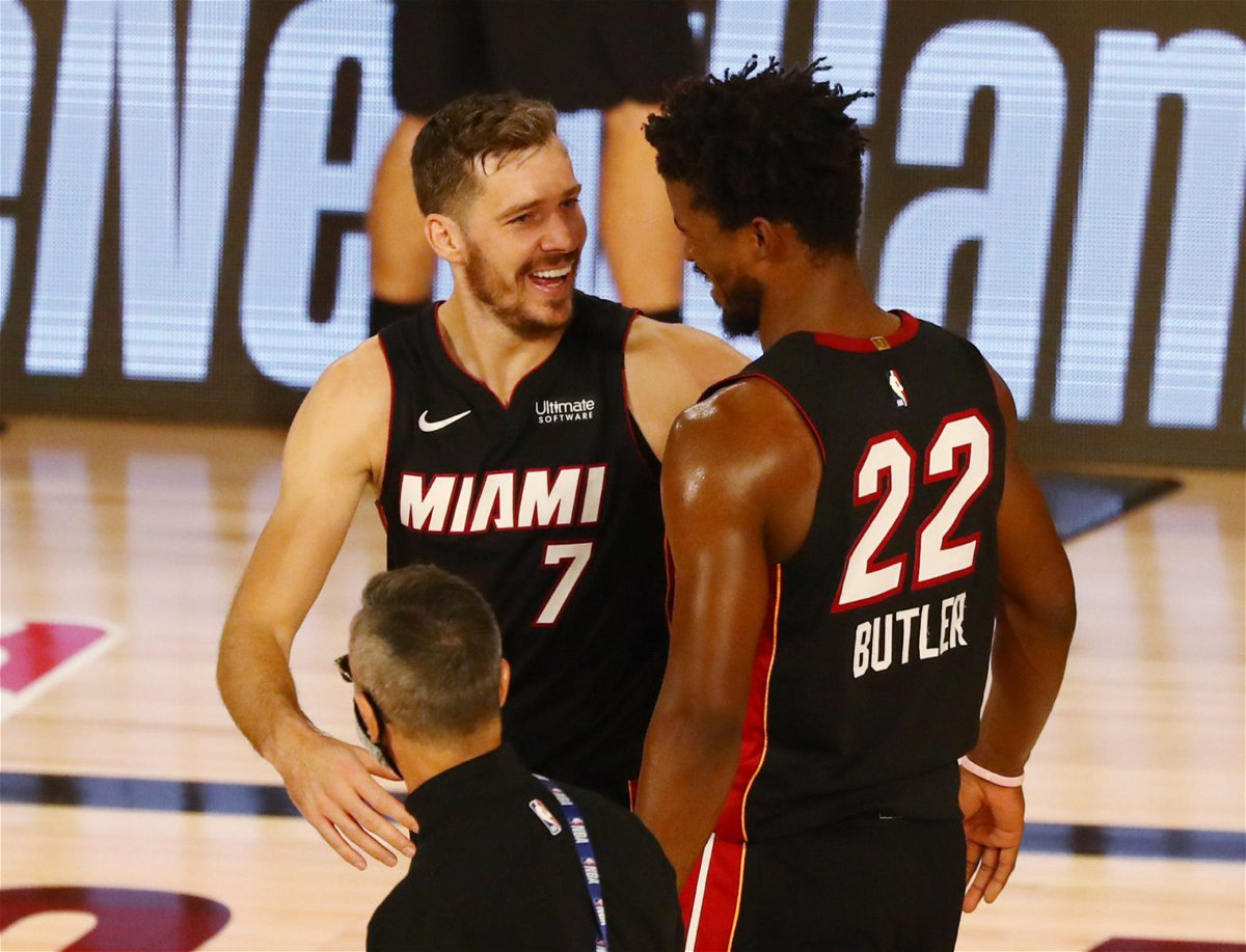 Miami Heat players Jimmy Butler and Goran Dragic share a light moment after Game 1 against the Milwaukee Bucks in the 2020 NBA Playoffs