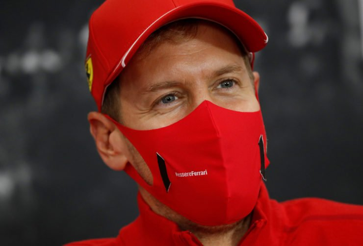 Ferrari driver Sebastian Vettel smiles behind the mask at a press conference