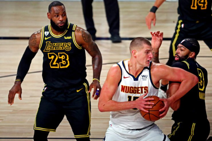 Denver Nuggets center Nikola Jokic drives to the basket against Los Angeles Lakers forward Anthony Davis and forward LeBron James