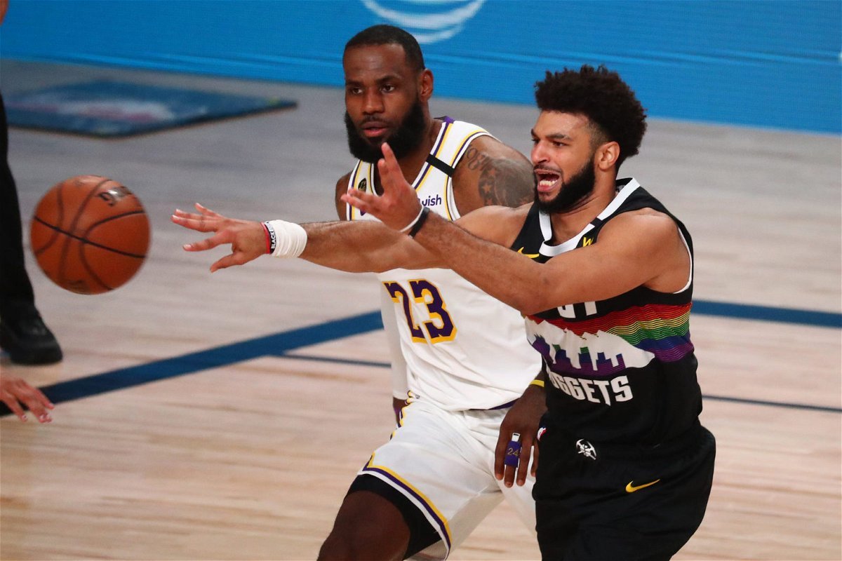 Denver Nuggets guard Jamal Murray passes the ball against LeBron James of Los Angeles Lakers