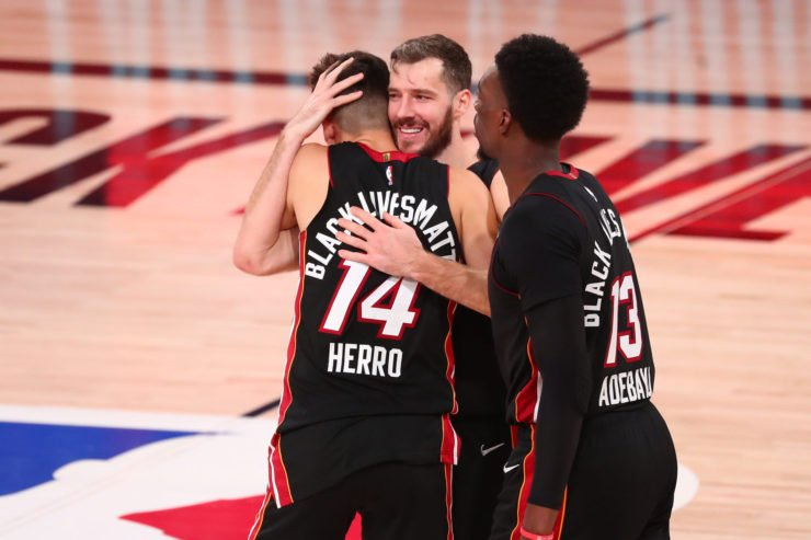 Veteran Goran Dragic shares a moment with Miami Heat youngsters Tyler Herro and Bam Adebayo