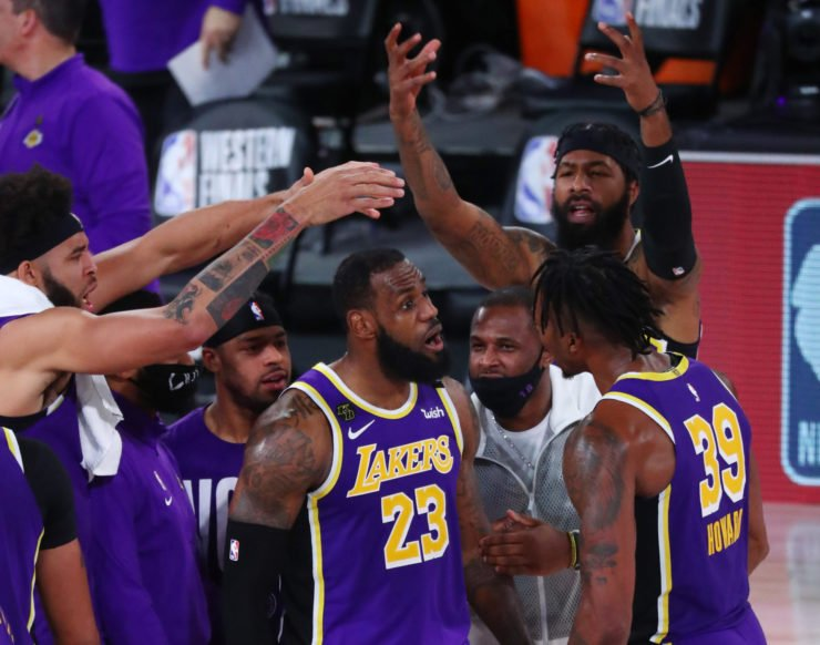 Los Angeles Lakers forward LeBron James and teammates celebrate in a huddle