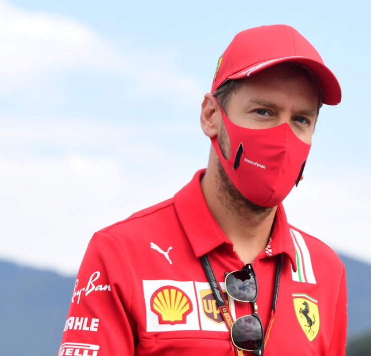 Ferrari driver Sebastian Vettel smiles behind the mask