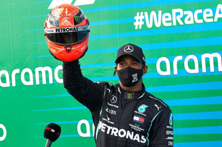 Lewis Hamilton holds aloft the helmet presented to him by Mick Schumacher after equaling Michael Schumacher's record at the Eifel GP
