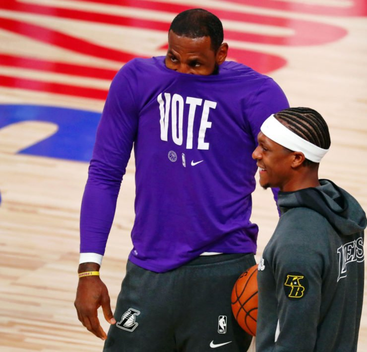 Los Angeles Lakers forward LeBron James (left) covers his nose and mouth with his shirt as he talks with guard Rajon Rondo (9) before game three of the 2020 NBA Finals against the Miami Heat