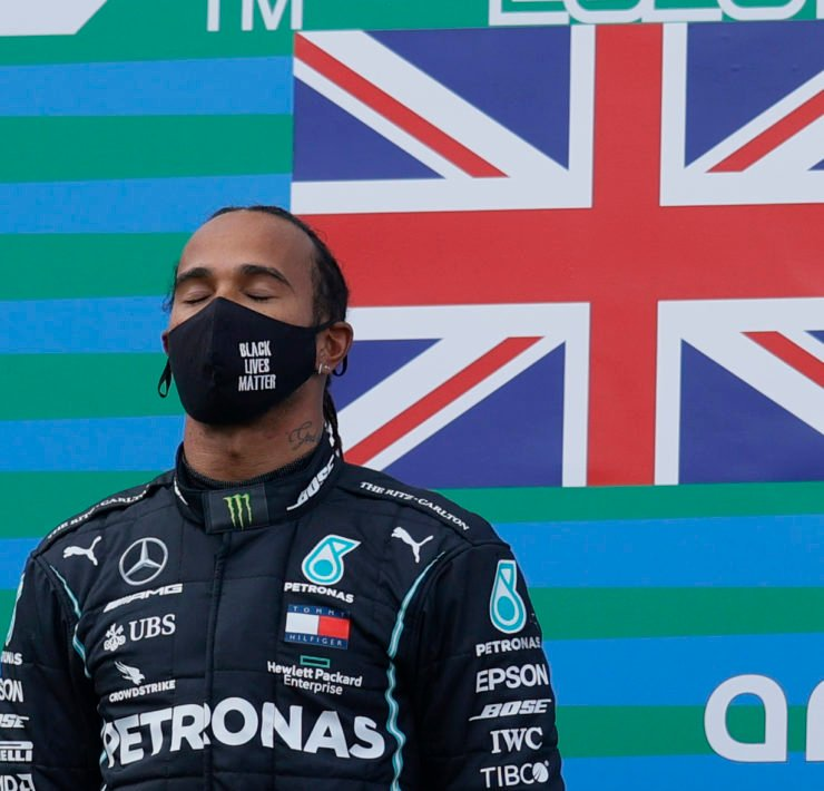 Lewis Hamilton closes his eyes atop the podium as the British national anthem plays after the Eifel GP