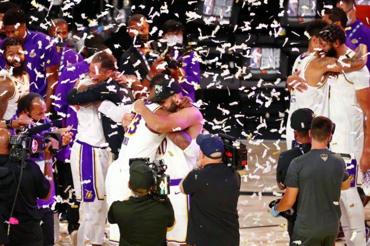 La Lakers队友Ja雷竞技app苹果版red Dudley和Lebron James在奖杯演示期间互相拥抱