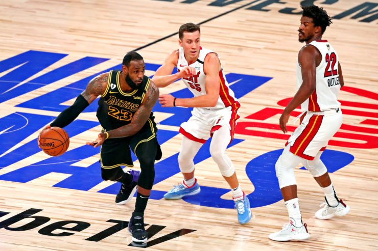 Miami Heat players Duncan Robinson and Jimmy Butler guarding Lakers' forward LeBron James