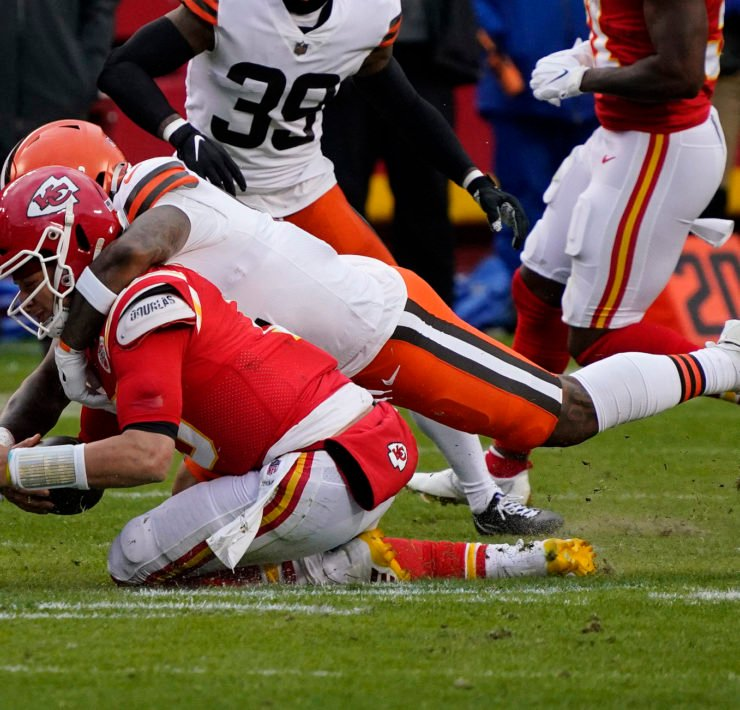 Kansas City Chiefs QB Patrick Mahomes tackled by Cleveland Browns defensive player.