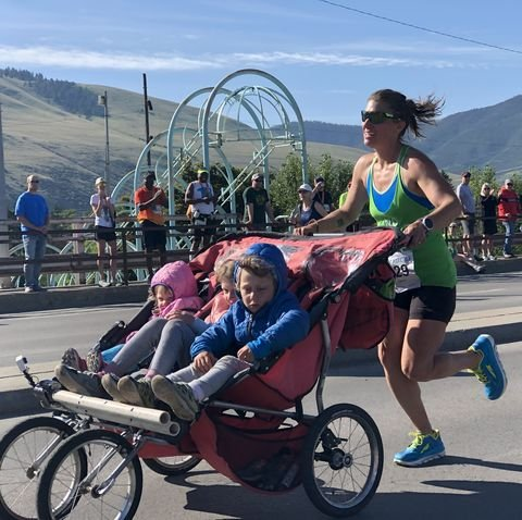 Woman (Cynthia Arnold) pushing a three kids in a stroller at Missoula Marathon